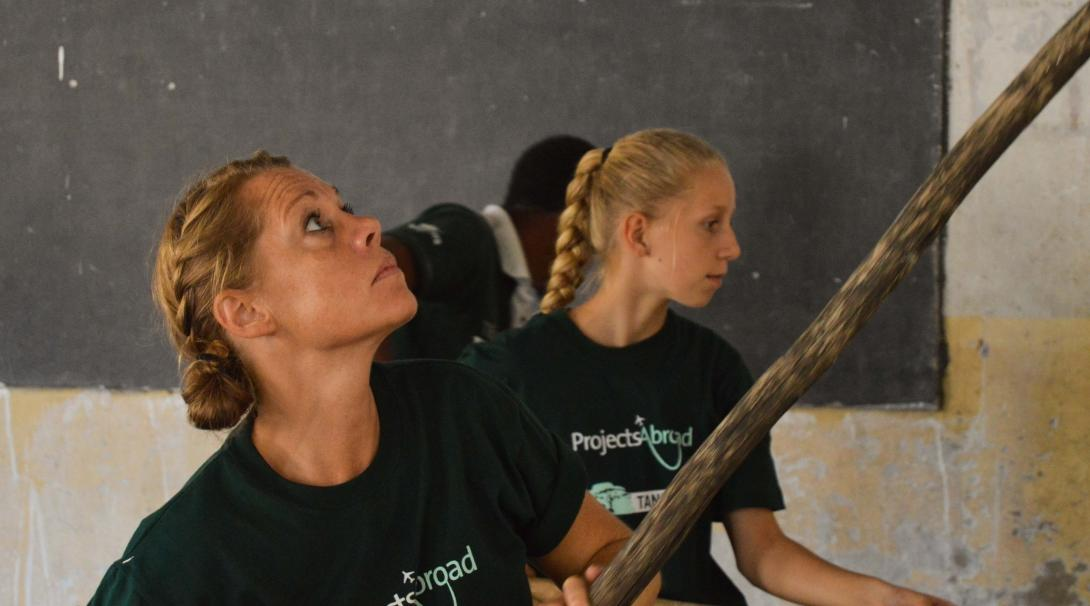 A mother and daughter volunteering overseas together help paint a classroom in Tanzania, Africa.